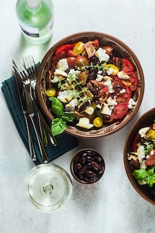 Italian traditional tuscan panzanella salad with fresh tomatoes and cheese in clay plates and white wine in a bottle and glasses .
