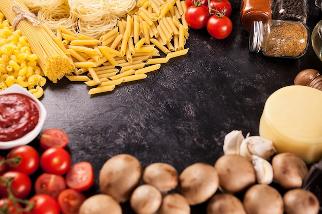 暗い木製のヴィンテージの背景にイタリアの未調理スパゲッティと生パスタ