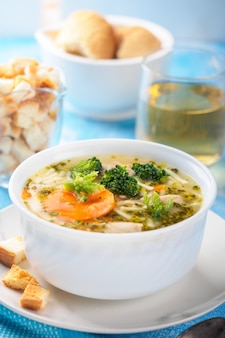 Italian vegetable soup with broccoli carrots and noodles in chicken broth
