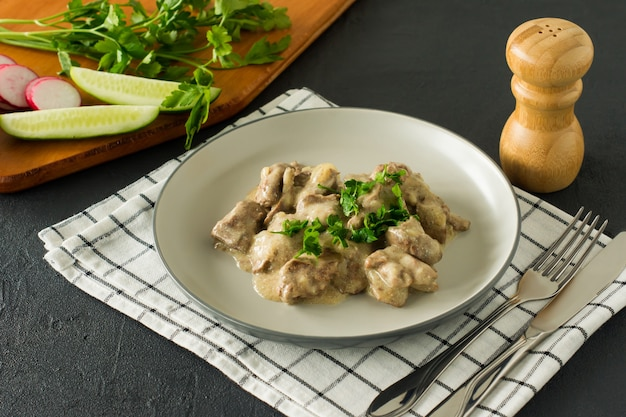대리석 접시에 구운 닭 간과 양파를 곁들인 이탈리아 통곡물 파스타
