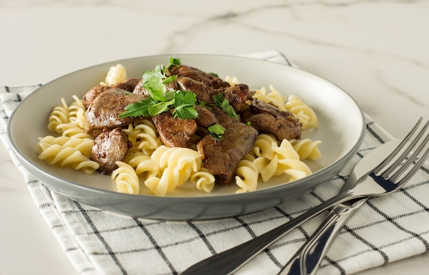 Italian whole grain pasta with roasted chicken liver and onions served on a plate on marble