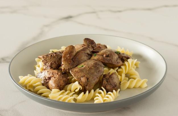 구운 닭 간을 곁들인 이탈리아 통곡물 파스타는 대리석 배경의 접시에 제공됩니다.