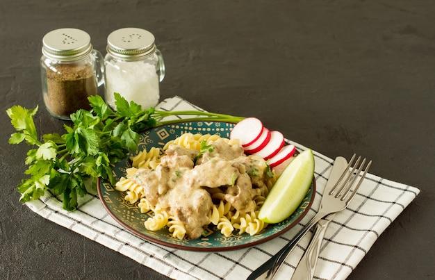 구운 닭고기 간을 곁들인 이탈리아 통곡물 파스타는 대리석 배경의 접시에 제공됩니다.