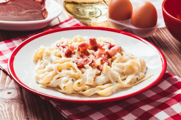 이탈리아 전통 요리 - 접시에 있는 파스타 탈리아텔레 카르보나라