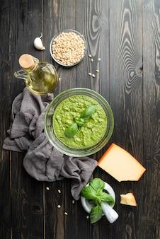 이탈리아 요리. 홈메이드 이탈리안 페스토 소스를 준비합니다. 재료를 넣은 그릇에 신선한 페스토, 검은색 나무 테이블에 평평한 위쪽 전망, 복사 공간