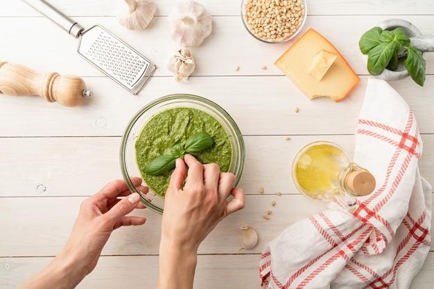 이탈리아 요리. 홈메이드 이탈리안 페스토 소스를 준비합니다. 재료가 담긴 그릇에 신선한 페스토, 흰색 나무 테이블에 평평한 평면도, 복사 공간