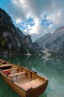 イタリア。ドロミテの山々とブラス湖のボート、秋の風景。
