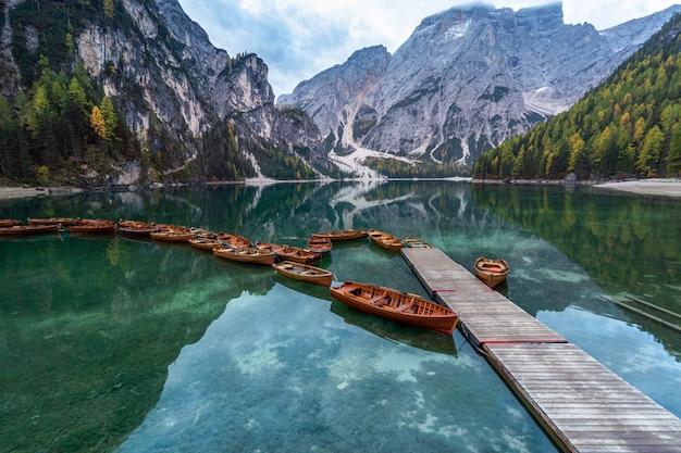 イタリア。ドロミテの山々とブラス湖のボート、秋の風景、垂直。