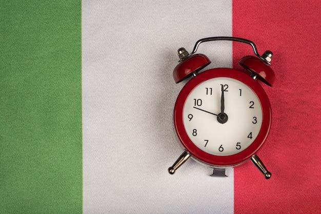 이탈리아 국기와 빈티지 알람 시계를 닫습니다. 이탈리아를 배울 시간입니다.
