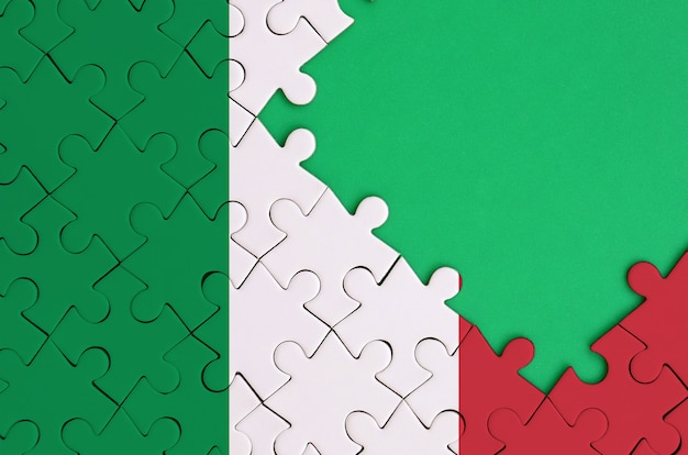 Italy flag is depicted on a completed jigsaw puzzle with free green copy space on the right side