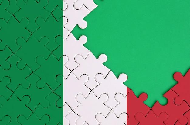 이탈리아 국기는 오른쪽에 무료 녹색 복사 공간이있는 완성 된 직소 퍼즐에 그려져 있습니다.