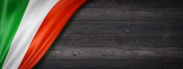 Флаг италии на черной деревянной стене. горизонтальный панорамный баннер.