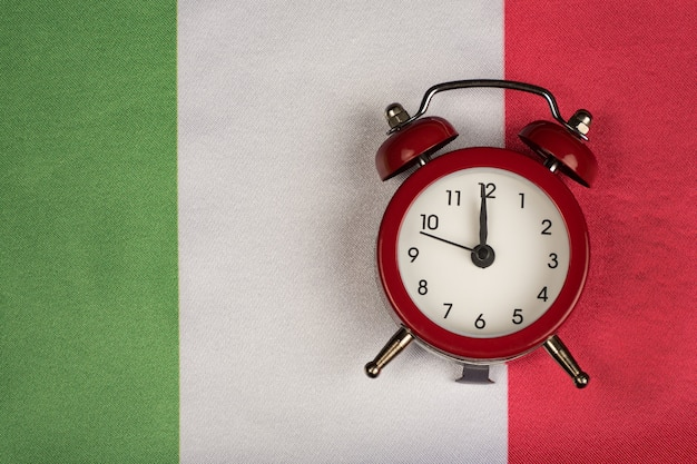 Italy flag and vintage alarm clock close up. time to learn italy.
