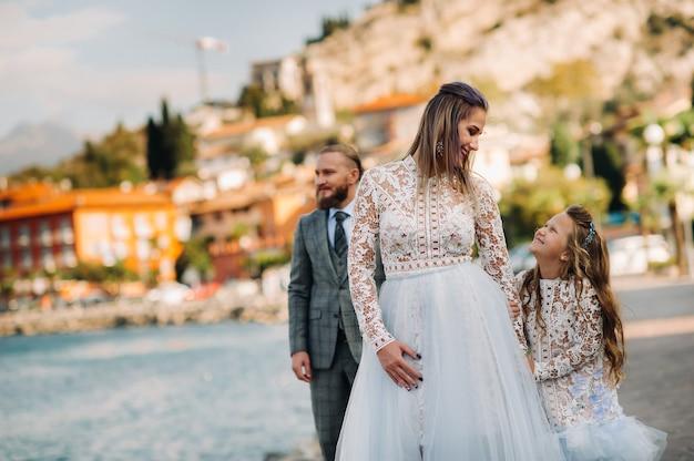 Италия, озеро гарда. красивая семья на берегу озера гарда в италии у подножия альп. отец, мать и дочь в италии.