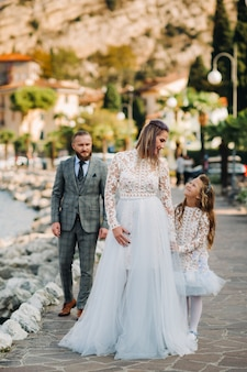 Italy, lake garda. beautiful family on the shores of lake garda in italy at the foot of the alps. father, mother and daughter in italy.