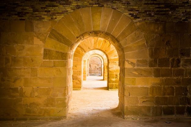Италия - старый замок сиракуз в сицилии. арки из камня в перспективе.