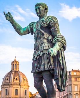 이탈리아, 로마 - 2020년 8월: 청동으로 만든 카이사르 황제의 동상. 자연 일출 빛입니다. 지도력과 권위의 고대 역할 모델.