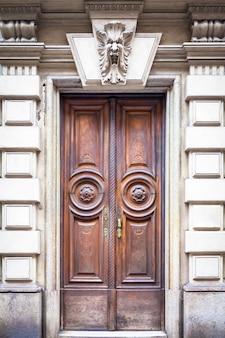 イタリア、トリノ。この都市は、2つの世界的な魔法の三角形の角として有名です。この古いドアは、過去100年にわたってガーゴイルによって守られてきました。