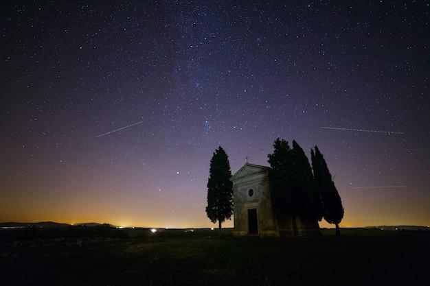 이탈리아. 투스카니. 필드에 외로운 예배당과 사이프러스 나무. 무수히 많은 별이있는 밤하늘