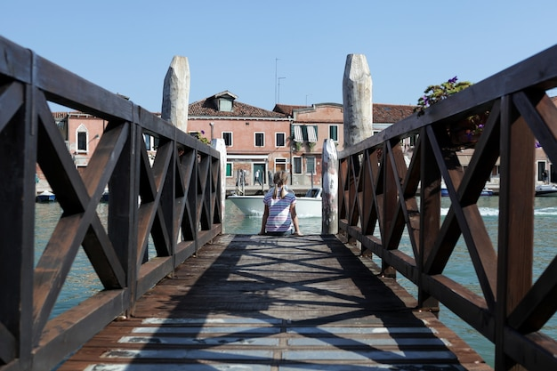 Italy, venetian lagoon, murano island. girl with pigtails sits on edge of wooden pier