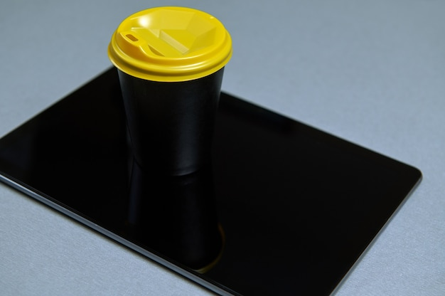 Item photograph. copy space. coffee in black paper glass with a yellow lid on a black tablet. top view on a gray background