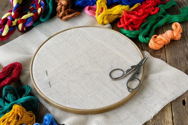 刺繡用アイテム。古い木製のフープ、カラフルなフロスの糸と帆布。