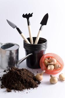 家庭で球根植物を植えるためのアイテム。土地、じょうろ、プラスチックポット、シャベル、球根