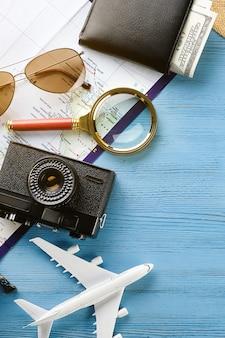Предметы для летнего отдыха: фотоаппарат, солнцезащитные очки, деньги в кошельке, карта или план путешествия. туристическая раскладка - набор и аксессуары путешественника на деревянной поверхности
