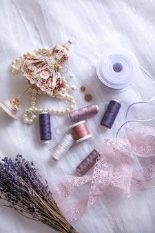 Изделия для пошива, катушки с нитками, иглы, ленты, кружево, пуговицы и вид сверху жемчужного ожерелья