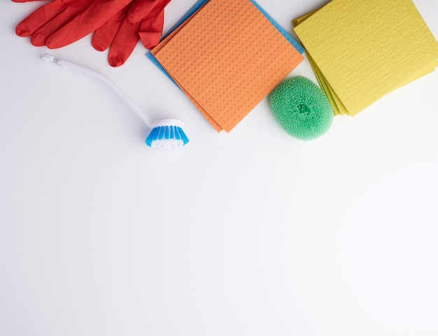 Items for home cleaning with red rubber gloves, brush, multi-colored sponges for dusting