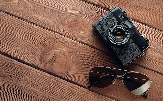 Items for summer holidays: camera, sunglasses. travel accessories on a wooden background. tourist layout-set of a street photographer.