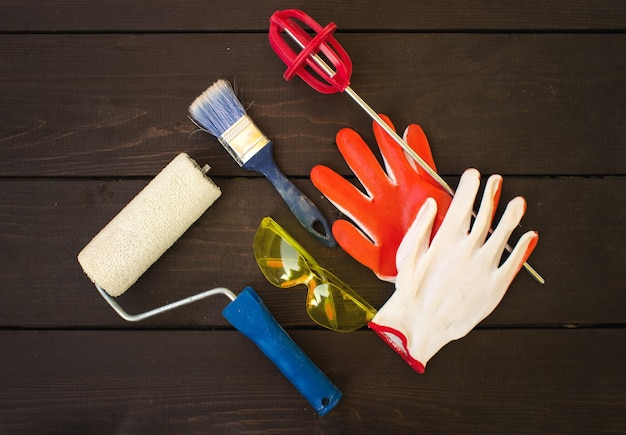 Items and tools of professional painter on wooden background. painter and decorator work table