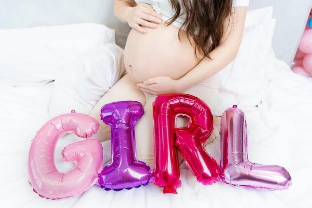 その女の子のベビーシャワーの風船と碑文の女の子の妊娠中の腹