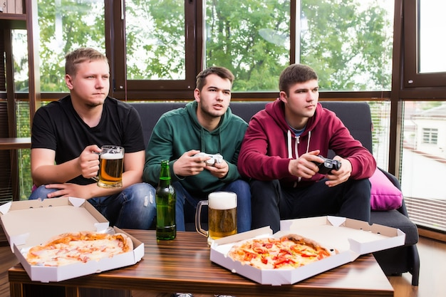 Это победа. возбужденные счастливые веселые мужчины играют в видеоигры с пивом и пиццей