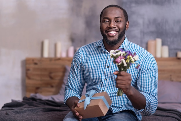 Its all for you. delighted young african man holding gift and flowers preparing for giving them to his girlfriend.