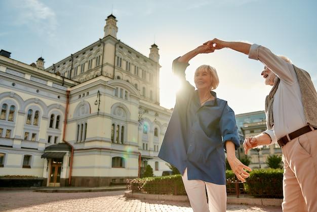 美しくて幸せな年配のカップルが一緒に踊るだけでいつも楽しい
