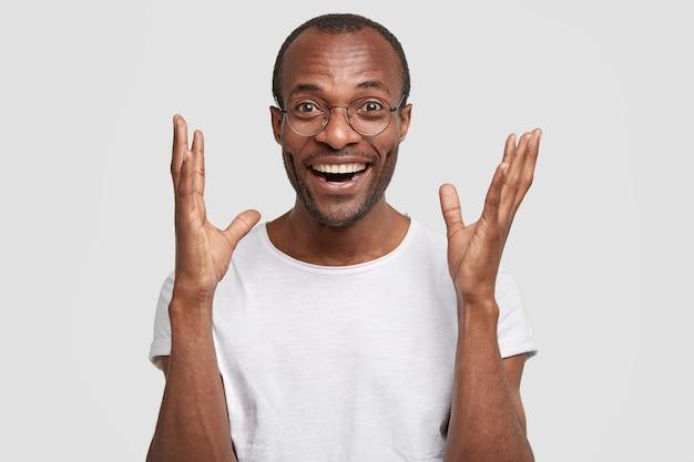 놀랍고 굉장합니다! 즐거운 어두운 피부를 가진 남자는 행복으로 손을 들고 긍정적 인 표현을 가지고 있습니다.