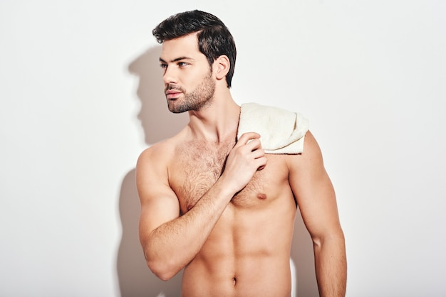 Its bathtime handsome man standing shirtless holding white towel isolated over white background