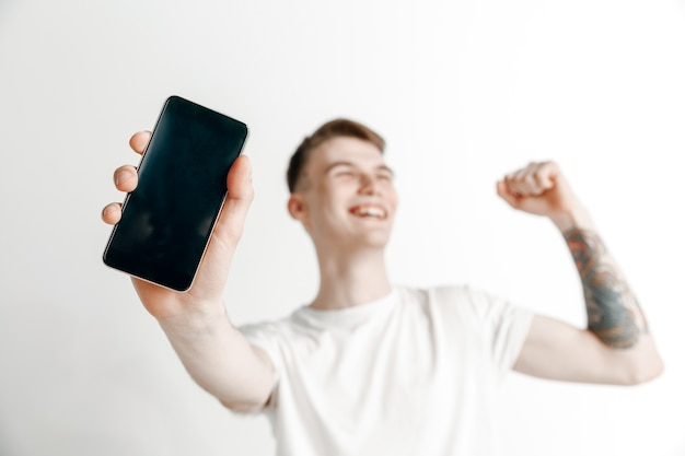 춥다. 좋은 소식. 나처럼하세요. 스마트 폰 화면을 표시 하 고 회색 배경에 고립 확인 서명 서명 젊은 잘 생긴 남자. 인간의 감정, 표정, 광고 개념.