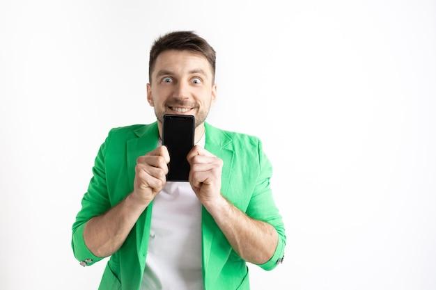 Это круто. хорошие новости. сделай так, как я. молодой красавец показывает экран смартфона и подписывает знак ок, изолированные на сером фоне. человеческие эмоции, выражение лица, рекламная концепция.