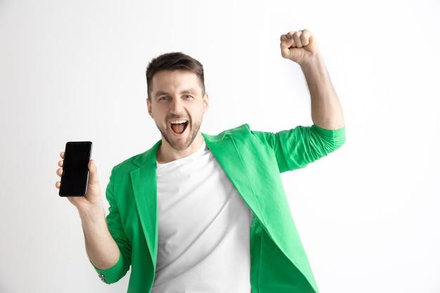 춥다. 좋은 소식. 나처럼하세요. 스마트 폰 화면을 표시 하 고 회색 배경에 고립 된 확인 서명 서명 젊은 잘 생긴 남자. 인간의 감정, 표정, 광고 개념.