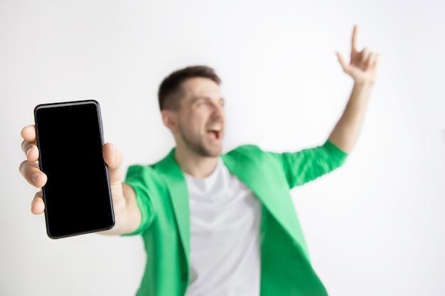 かっこいいね。朗報です。私のようにしてください。スマートフォンの画面を表示し、灰色の背景で隔離のokサインに署名する若いハンサムな男。人間の感情、顔の表情、広告のコンセプト。
