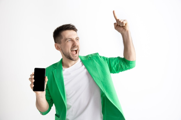 Its cool. good news. do that like me. young handsome man showing smartphone screen and signing ok sign isolated on gray background. human emotions, facial expression, advertising concept.