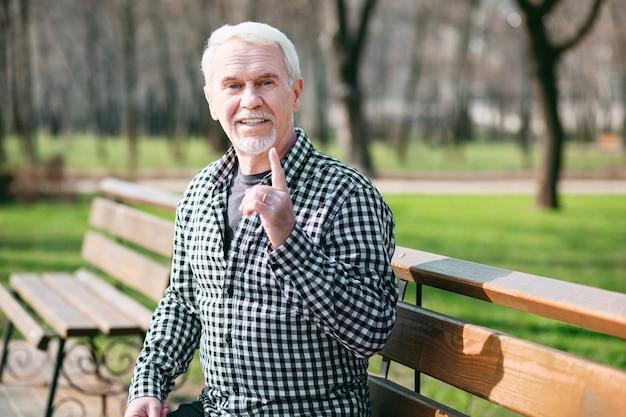 Это опасно. привлекательный старший мужчина позирует на скамейке и поднимается пальцем