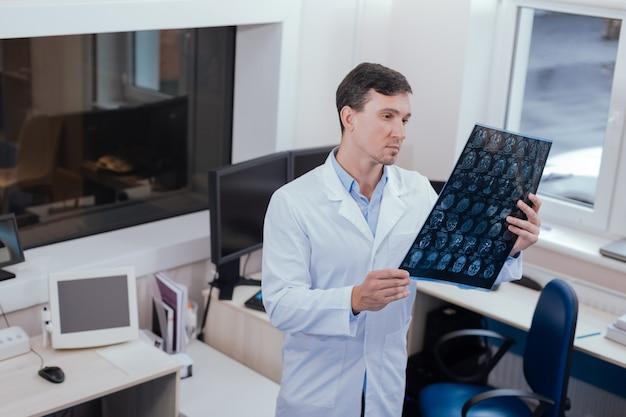 Сложно решить. серьезный приятный мужчина-радиолог держит снимок рентгеновского снимка и смотрит на него, думая о возможном диагнозе