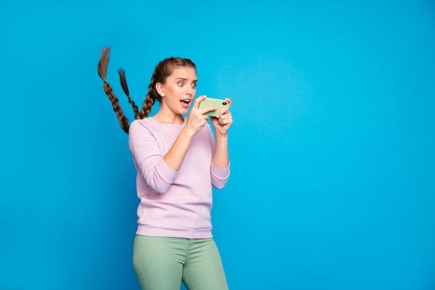 それは私です?信じられない!驚いたブロガーの若い女の子の肖像画は、セルフィーの悲鳴を上げた後、携帯電話に見えます。
