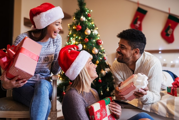Its time for presents ! group of three happy friends sharing new years presents. sitting in a room with beautiful new years decoration.
