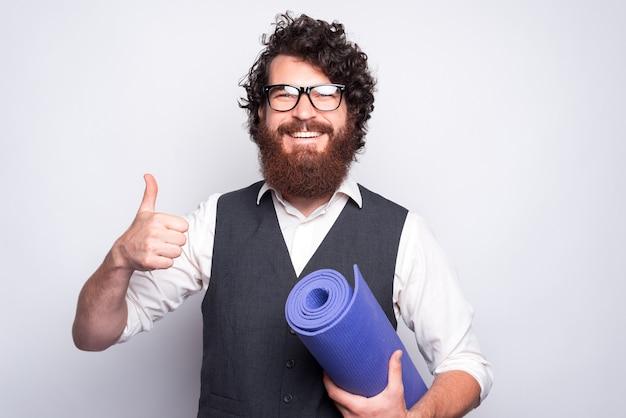 Пора пойти в тренажерный зал, улыбающийся бородатый мужчина в костюме показывает большой палец вверх и держит коврик для йоги