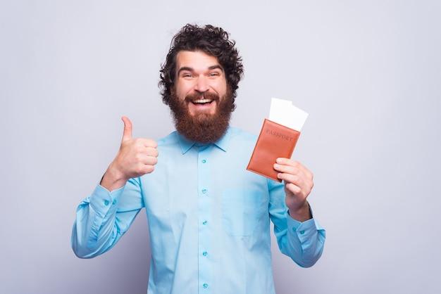 Пора путешествовать, взволнованный бородатый мужчина в рубашке показывает жест вверх пальцем и паспорт с билетами на самолет