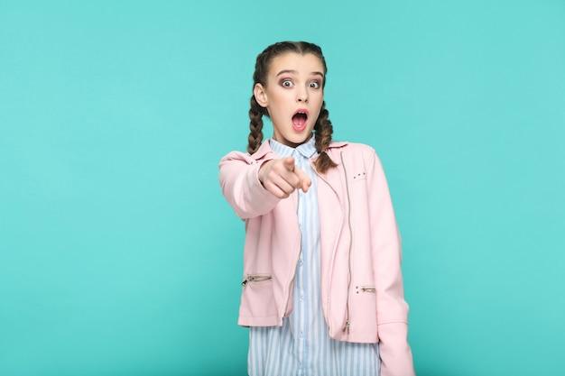 Это невероятный портрет красивой милой девушки, стоящей с макияжем и коричневой прической в косичку в полосатой голубой рубашке и розовом пиджаке. крытый, студийный снимок, изолированные на синем или зеленом фоне.